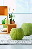 Convex green stools on split leather rug and cubic plastic shelving unit