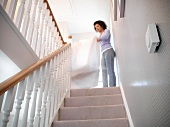 Woman shaking out sheets on staircase