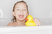 Girl playing with rubber duck in bath