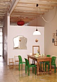 Green plastic chairs around wooden table next to wall of module installed in loft-style interior