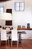 Dining area with massive table and upholstered white chairs in front of collection of jugs and stoneware pots on shelf on whitewashed wall with lattice windows in gable end wall