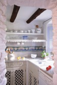 Nostalgic, Mediterranean kitchen with wooden cupboards and wall-mounted shelves with lace trim