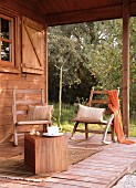 Simple wooden veranda with comfortable rocking chairs and wooden cube as side table