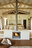 Masonry fireplace built in centre of open-plan interior in front of dining area and kitchen on platform in Mediterranean house