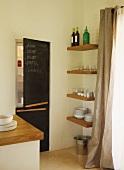 Moderne Küchenecke - Eingebaute Kühlschrankkombination mit Schiefertafel auf Türfront neben Regalböden mit Geschirr