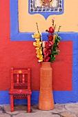 Farbenfrohe Wandgestaltung; davor eine Terrakottavase mit Kunstrosen und ein bemalter Kinderstuhl