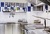 Moderne Restaurantküche mit Edelstahlfronten und weissen Wandfliesen