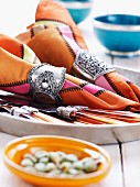 Napkins in ornate napkin rings and cutlery on tray