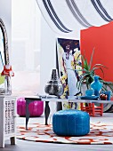 Decorative metal and blue glass vessels on low table and brightly coloured, Moroccan pouffes