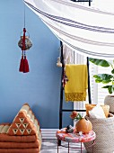 Exotically inspired interior design with lantern and tassels hanging above Thai floor cushions