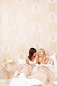 Smiling women relaxing together on bed