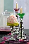 Lit candles in mercury glass candlesticks on glass dish