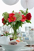 Summer bouquet in vase and white place settings with wine glasses on table