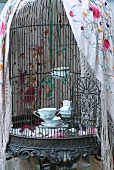 Windlichter aus alten Tassen in einem Käfig