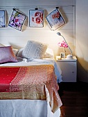 Bedspread on simple bed below floral photos hanging from clips on white wooden wall