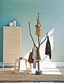 Pattern of light and shade on stylised tree as coat rack and modern stool in front of shoe cabinet against pastel blue wall