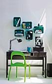 Grasgrüner Kunststoff Stuhl vor schwarzem Holz-Sekretär und einzelne Kunststoff-Wandbord-Boxen in smaragd mit gerundeten Ecken an der Wand