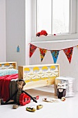 Boxy, wooden, DIY child's bed with painted headboard and foot and toys on floor in front of window with string of bunting