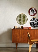 Retro-patterned plates hanging on wall above fifties-style wooden sideboard