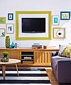 Fernseher und Buchstabensymbole mit Bilderrahmen an der Wand über traditionellem Sideboard aus Holz