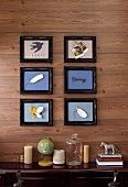 Objet d'art in picture frames on wooden wall above various ornaments on sideboard