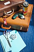 Utensils for converting old suitcases (leather suitcases, cordless screwdriver, spray glue, scissors and screws)