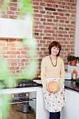 woman in kitchen smiling at viewer