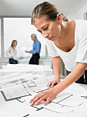 Woman working on blue prints