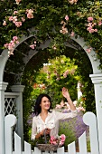 Woman with flowers waving from gate