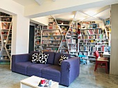 Purple sofa in front of floor-to-ceiling book shelves which cover all the walls of a modern living room