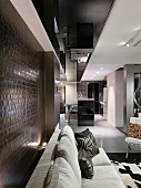 Sofa upholstered in light fabric in front of a wall clad in crocodile style leather and view into an open kitchen area
