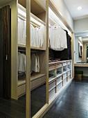 Offener Schrank mit aufgehängten Hemden auf Kleiderstange in Ankleide