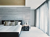 Elegant designer bedroom with a double bed in front of a room divider tiled in gray next to a window with floor-to-ceiling curtains