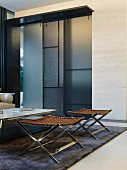 Stool with rattan seat and metal frame and coffee table in a modern living room