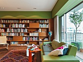 Designer sofa in front of a bank of windows and wooden book shelves on a green wall in a modern living room