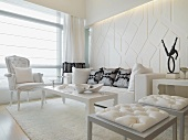 Living room with post modern stools in front of a coffee table and white neo-baroque armchair
