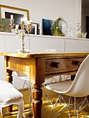 Antique, rustic wooden table with drawer and Bauhaus shell chair in front of half-height sideboard