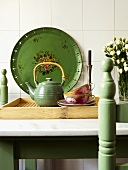 Tea set on tray in front of green, painted metal platter leaning on white tiled wall
