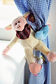 Monkey soft toy as humorous curtain tie-back in child's bedroom
