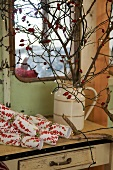 Branches of rosehips with fairy lights in china jug on vintage table below window
