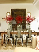 Retro metal chairs around wooden table with branches of berries in vases in front of tapestry hanging on wall