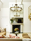 Vintage chandelier above sofa set in front of open fireplace in living room with traditional atmosphere