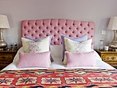 Double bed with scatter cushions against headboard with pink upholstery
