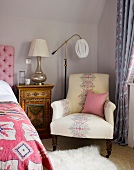 Upholstered armchair and vintage standard lamp next to painted bedside cabinet against pastel wall in corner of bedroom