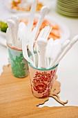 Plastic cutlery in beakers on wooden board