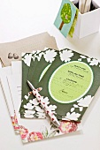 Invitation cards and pen in front of white cardboard storage box