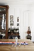 Holztisch mit französischem Fahnenband, im Hintergrund Beistelltisch mit Weinflaschen und antiker Vitrinenschrank