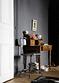 Antique writing desk in front of a dark gray wall next to a white door
