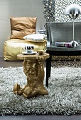 Gold side table with garden gnome as base and chair on flokati rug in front of gold floor cushion