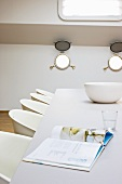 Open book and china bowl on table with white shell chairs in houseboat cabin